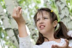 As preensões triguenhas bonitos da menina encontraram a larva Fotografia de Stock