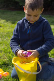 As quebras novas do menino abrem um ovo da páscoa sobre uma cubeta enchida Fotos de Stock Royalty Free