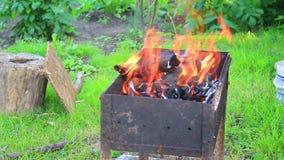As queimaduras do fogo na grade do ferro na grama video estoque