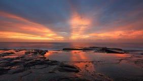 As raias da luz vermelha alaranjada na onda do nascer do sol ondulam Imagens de Stock Royalty Free