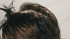 As raizes cinzentas cobertos de vegetação de uma mulher de meia idade que que colore seu cabelo com escova especial Cabelo escuro vídeos de arquivo