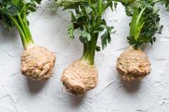 As raizes de aipo com verde saem em uma tabela branca Fotografia de Stock Royalty Free