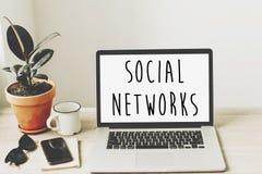As redes sociais text na tela do portátil no desktop de madeira com pho imagem de stock royalty free
