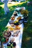 As refeições na tabela da abundância como uma parte da cerimônia de casamento natural realizaram na natureza Imagem de Stock
