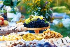 As refeições na tabela da abundância como uma parte da cerimônia de casamento natural realizaram na natureza Fotografia de Stock