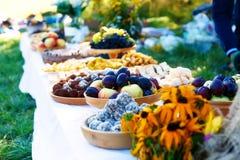 As refeições na tabela da abundância como uma parte da cerimônia de casamento natural realizaram na natureza Fotografia de Stock Royalty Free