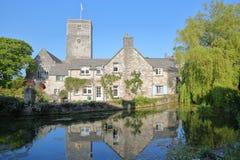 As reflexões do moinho Pond a igreja das casas de campo e do ` s de St Mary no monte da igreja, Swanage foto de stock