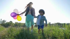 As relações amigáveis, crianças alegres em vidros com os balões nas mãos correm na grama verde perto do rio à luz de video estoque