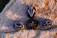 As rochas pintadas que indicam a noiva, noivo, ` EU FAÇO, ` e um tux Fotos de Stock