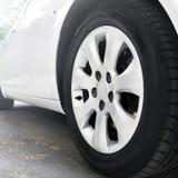 As rodas de carro fecham-se acima em um fundo do asfalto Carro branco imagem de stock