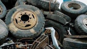 As rodas oxidadas velhas de veículos diferentes são despejadas em um montão em um território da fábrica de tratamento waste no di vídeos de arquivo