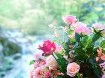 As rosas artificiais florescem o arranjo do ramalhete contra o borrão verde Foto de Stock