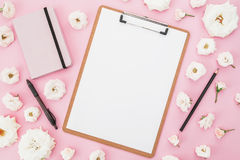 As rosas brancas florescem com prancheta, caderno e pena no fundo cor-de-rosa Configuração lisa, vista superior Fundo fêmea do ne imagem de stock