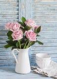 As rosas cor-de-rosa em um branco esmaltaram o jarro e bacias brancas cerâmicas no fundo rústico de madeira azul Da cozinha vida  Fotografia de Stock Royalty Free