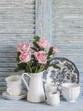 As rosas cor-de-rosa em um branco esmaltaram o jarro, louça do vintage no fundo rústico de madeira azul Da cozinha vida ainda no  Fotos de Stock Royalty Free