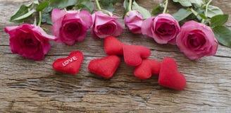 As rosas e o coração vermelho descansam na placa de madeira velha, dia de Valentim b Fotografia de Stock Royalty Free