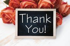 As rosas e o quadro-negro alaranjados com palavras agradecem-lhe Foto de Stock