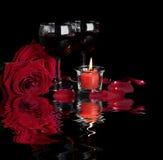 As rosas e o vinho tinto no preto refletiram em uma água Fotografia de Stock Royalty Free