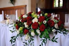 As rosas vermelhas decoram a tabela do casamento Fotos de Stock
