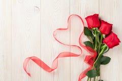 As rosas vermelhas e o coração dão forma à fita sobre a madeira Imagem de Stock
