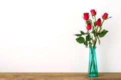 As rosas vermelhas florescem o ramalhete no vaso verde no fundo branco Fotografia de Stock Royalty Free