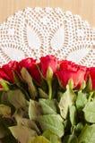 As rosas vermelhas no branco fazem crochê a toalha de mesa Fotografia de Stock Royalty Free