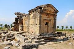 As ruínas da cidade antiga de Hierapolis ao lado das associações do travertino de Pamukkale, Turquia túmulo imagens de stock
