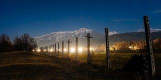 As ruínas de um feno velho submetem na noite com luzes e montanhas Imagens de Stock Royalty Free