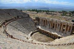 As ruínas do anfiteatro da cidade antiga de Hierapolis no fundo das montanhas perto de Pamukkale, Turquia fotografia de stock royalty free