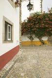 As ruas e a planta estreitas da buganvília na vila de Obidos fundaram pelos Celts em 300 BC, Portugal fotografia de stock