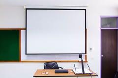 As salas de aula brancas estão atualmente disponíveis com mesas e cadeiras do estudante fotografia de stock