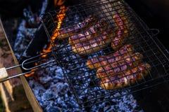 As salsichas de carne de porco da repreensão na grade raspam sobre os carvões fotografia de stock royalty free