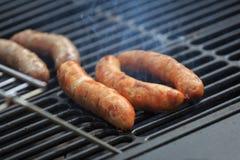 As salsichas de carne de porco apetitosas são cozinhadas na grade com um fumo fotografia de stock royalty free