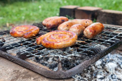 As salsichas saborosos que cozinham sobre os carvões quentes em um assado ateiam fogo para fora Fotos de Stock Royalty Free