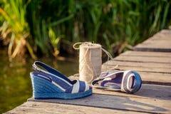 As sandálias azuis da sarja de Nimes encontram-se na embreagem de madeira no lago Foto de Stock