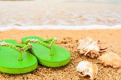 As sandálias das mulheres na praia na linha costeira Fotografia de Stock
