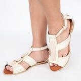 As sandálias de couro bege com ouro aplicaram nos pés o mujere no fundo branco Fotografia de Stock Royalty Free