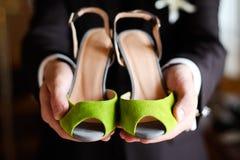 As sapatas da dama de honra esverdeiam nas mãos do noivo Imagem de Stock