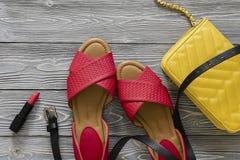 As sapatas de couro das mulheres e sandálias lisas vermelhas dos acessórios, h amarelo Foto de Stock