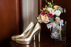 As sapatas do casamento dourado e o ramalhete nupcial delicado com laço curvam-se foto de stock