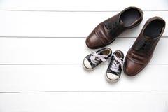 As sapatas do pai e do filho no fundo branco de madeira - conceito t fotos de stock