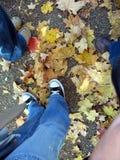 As sapatas do pessoa do detalhe com folhas da queda Imagens de Stock Royalty Free