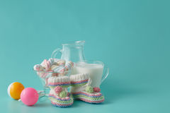 As sapatas e o vintage de bebê chocalham com vidro de leite Fotos de Stock Royalty Free