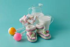 As sapatas e o vintage de bebê chocalham com vidro de leite Foto de Stock Royalty Free