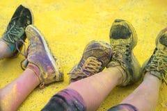 As sapatas e os pés coloridos dos adolescentes no evento da corrida da cor Imagens de Stock
