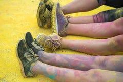 As sapatas e os pés coloridos dos adolescentes no evento da corrida da cor Imagens de Stock Royalty Free