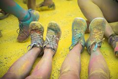As sapatas e os pés coloridos dos adolescentes no evento da corrida da cor Foto de Stock