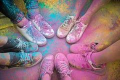 As sapatas e os pés coloridos dos adolescentes no evento da corrida da cor Fotografia de Stock Royalty Free