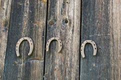 As sapatas retros do cavalo penduram a parede rural de madeira do prego Imagens de Stock Royalty Free
