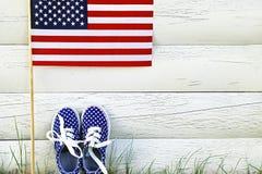 As sapatilhas das crianças americanas e a bandeira do Estados Unidos da América Fotos de Stock